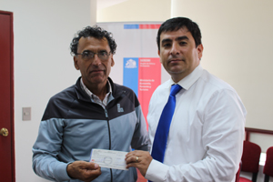 Rubén Ramos Meneses, racibe el cheque de manos del SEREMI de Economía Franz Castro Cabezas.